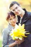 Couple holding autumn leaves. Lovers spend sunny day in the autumn park, they hold autumn leaves Royalty Free Stock Photography