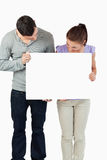 Couple holding banner together and looking down Royalty Free Stock Photography