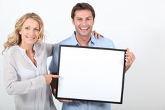 Couple holding a blank board. Ready for image or text Royalty Free Stock Images