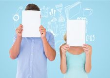 Couple holding blank page in front of their face against blue background Stock Photo