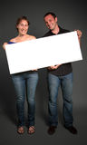 Couple holding a blank sign Royalty Free Stock Photo