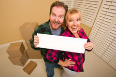 Couple Holding Blank Sign in Room with Boxes Stock Images