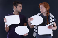 Couple holding blank speech bubbles. Young couple holding blank speech bubbles, dark background Royalty Free Stock Photo