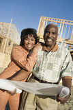 Couple Holding Blueprint Against House Construction Site. Portrait of a smiling couple holding blueprint in front of house construction site Stock Photo