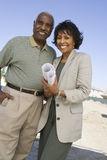 Couple Holding Blueprint At An Empty Land Stock Image