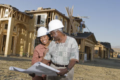 Couple Holding Blueprint In Front Of Incomplete House. Happy African American senior couple holding blueprint in front of house under construction Royalty Free Stock Photo