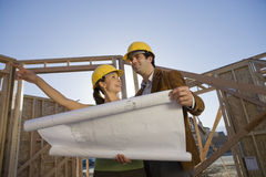 Couple Holding Blueprint At Site Royalty Free Stock Images