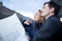 Couple holding blueprints admiring building Royalty Free Stock Photography