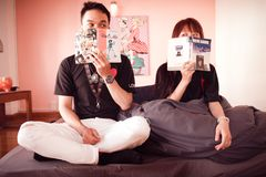 Couple Holding Books Sitting on Bed Royalty Free Stock Photography