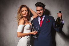 Couple holding a bottle of champagne saying cheers Royalty Free Stock Image