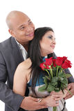 Couple holding a bouquet of red roses looking at a copyspace Royalty Free Stock Photography