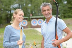 Couple holding bows and arrows Stock Photo