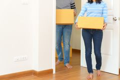 Couple holding boxes into their home - moving house concept. royalty free stock photos