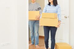 Couple holding boxes into their home - moving house concept. royalty free stock image