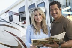 Couple Holding Brochure. Portrait of happy couple holding a brochure with tour bus in background Royalty Free Stock Photo