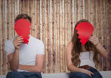 Couple holding broken heart in front of their faces. Separated couple holding broken heart in front of their faces Royalty Free Stock Photo