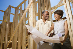 Couple Holding Building Plans on Construction Site Royalty Free Stock Images