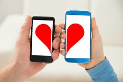 Couple holding cellphone with half heart symbol stock photography