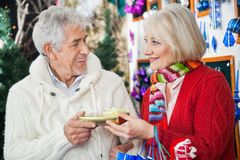 Couple Holding Christmas Gift At Store Stock Images