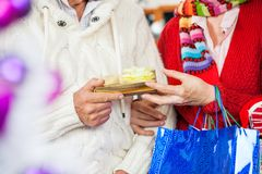 Couple Holding Christmas Present At Store Stock Photography