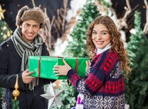 Couple Holding Christmas Present Together In Store Royalty Free Stock Photography