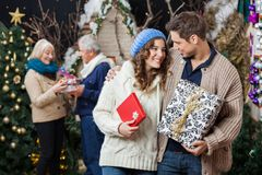 Couple Holding Christmas Presents With Parents In Royalty Free Stock Image
