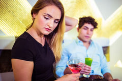 Couple holding cocktail glasses. Young couple holding cocktail glasses at nightclub royalty free stock photo