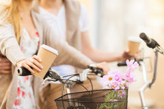 Couple holding coffee and riding bicycle Royalty Free Stock Photo