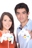 Couple holding control pads Royalty Free Stock Photos