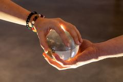 Couple holding a crystal ball together stock photo