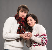 Couple holding cup of coffee on a gray background Stock Image