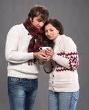 Couple holding cup of coffee on a gray background Stock Photos