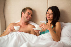 Couple holding cups in bed. Stock Image
