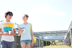 Couple holding disposable cups while walking at park Stock Image