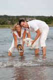 Couple holding dogs over water Stock Images