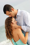 Couple holding each other with man kissing top of. A young woman is being held close by a man,  He is kissing the top of her head. With ocean waves in the Stock Photos