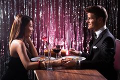 Couple holding each other's hand at dinner Stock Photos