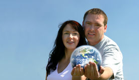 Couple Holding Earth. Focus begins on the faces and ends on the Earth. Hands are very soft focused. There is a semi-transparent atmosphere around the globe Royalty Free Stock Photos