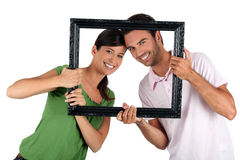 Couple holding empty art frame Stock Images
