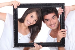 Couple holding empty frame Stock Image