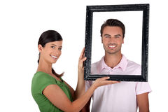 Couple holding empty picture frame Stock Photos