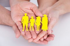 Couple holding family figure cut-out Royalty Free Stock Photos