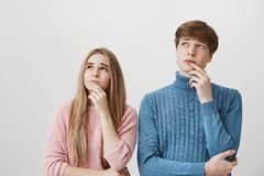 Couple holding fingers on chins, looking sidewards thinking about something, standing against gray wall. Fair-haired. Shot of couple holding their fingers on Royalty Free Stock Photography