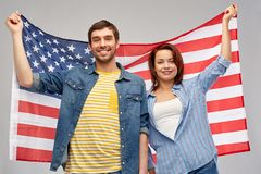 Couple holding flag of united states of america. Patriotism, independence day and national concept - happy couple holding flag of united states of america over stock image