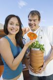 Couple holding flower pots in outdoors garden Stock Photography