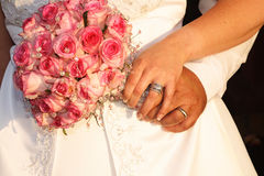 Couple holding flowers. Bridal Couple holding wedding bouquet made of pink roses stock images