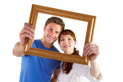 Couple holding frame ahead of them Royalty Free Stock Photos