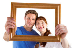 Couple holding frame ahead of them Stock Photos