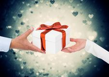 Couple holding gift against digitally generated green illuminated background. Close-up of couple holding gift against digitally generated green illuminated Royalty Free Stock Images