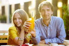 Couple holding glass of juice (focus on glass) Stock Image